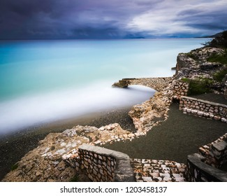 Seascape image taken with a long exposure of an old slave port in the Caribbean with dramatic clouds on the horizon