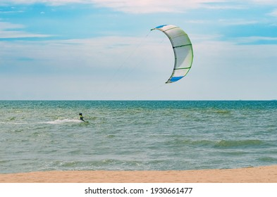 Seascape with kitesurfers in the waves.