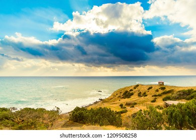 Seascape with large clouds and a small arbor, Cape Sarych, Crimea, Russia. Yellow mountain with bushes and trees, panorama of the Black Sea, a small red arbor on a hill, clouds with rays of the sun