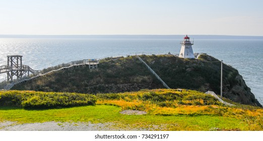 A seascape of the lighthouse on Cape Enrage, New Brunswick, Canada, on the rocky hill with the wooden walkway and fences creating angles
