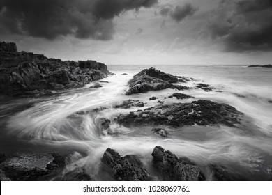 Seascape at low tide with moody clouds and pending storms and swirling ocean currents around the exposed rocks.