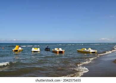 Seascape of the Maremma Tuscan coast with a row of pedalboats and a jet ski on the shore in summer, Marina di Castagneto Carducci, Livorno, Tuscany, Italy