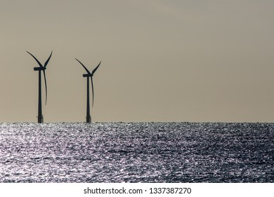 Seascape. Offshore wind farm turbines silhouette on beautiful sea horizon. Green energy sustainable resource background image with copy space.