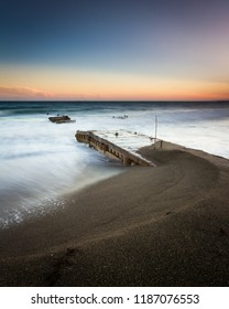 Seascape of an old pier at sunset
