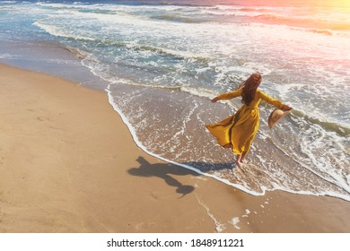 Seascape on a sunny day in summer. Woman on the beach, summertime. Young happy woman with hands in the air walks carefree on the seaside in yellow fluttering dress. View from above - Shutterstock ID 1848911221