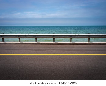 Seascape over the paved road and guardrail at Chapoquoit Rd in Falmouth on Cape Cod