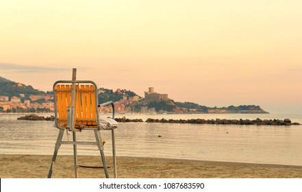 seascape, paradise beach, yellow chair and castle  landscape view Lerici Liguria, Italy