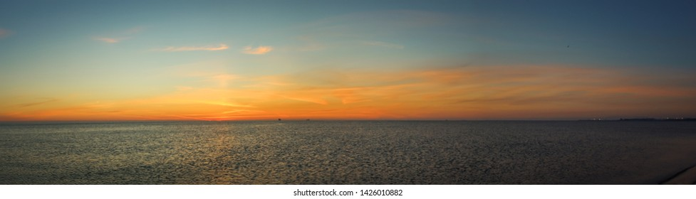 Seascape photos of a morning, golden sunrise at the sea and ocean. Small, little clouds and orange sunlight with dark water.