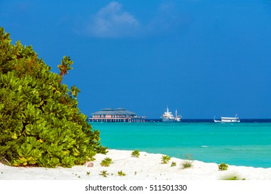 Seascape with pier and two ships, in the foreground blurred sandy beach, Maldives