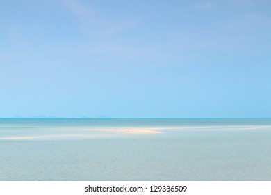 Seascape with puffy white clouds,sand and blue sky