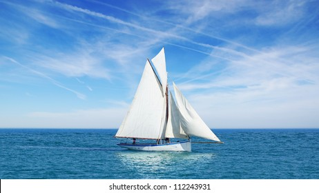 Seascape with sailboat the background of the blue sky.