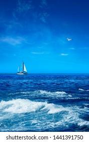 Seascape with sailboat on horizon over sunny blue sky