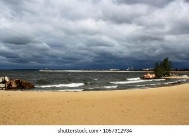 Seascape. Sandy beach. Gloomy cloudy sky.
