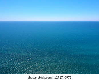 Seascape with sea horizon and clear deep blue sky. Horizontal vivid minimal landscape abstraction background backdrop. Get lost in a peaceful and misty ocean aerial view.