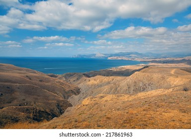 Seascape. Seacoast, yellow hills, mountains and capes. The calm sea and blue sky with white clouds. Photographed in the summer on a hot sunny day.