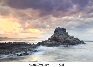 Seascape showing waves breaking against a rock on the coast with a cloudy stormy sky and the sun appearing in the background