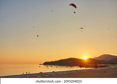 Seascape with silhouettes of the mountains and coast of sea at sunset. Paraglider flying over the beach of Oludeniz in golden sunlight. Turkish resort for summer holiday, leisure and paragliding.