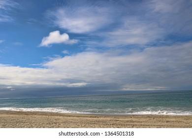 Seascape of a sky with clouds over a sandy beach near the ocean