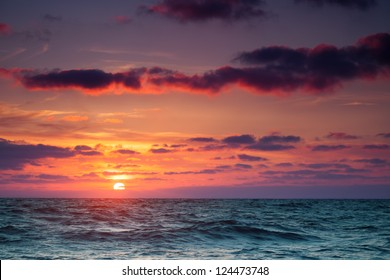 Seascape. Sun in the clouds at sunset over the sea