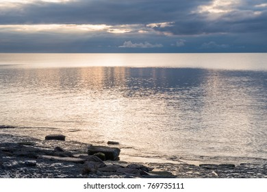 Seascape with sun reflections in the water and a dramatic sky