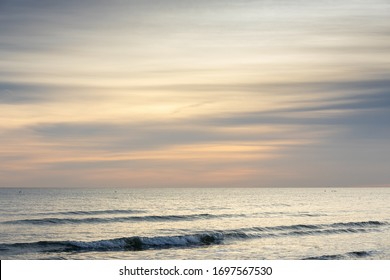 Seascape at sunset with muted colours in Autumn over a tranquil sea on the south coast of England.