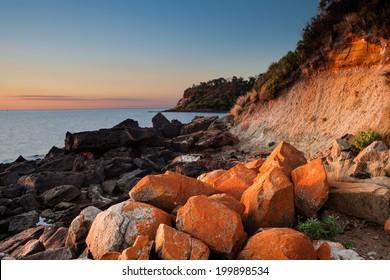 Seascape of Sunset with orange rocks on foreground