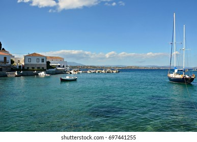 Seascape with the traditional, red clay roof tiled, white washed houses and the Greek fishing and sailing boats in Spetses island, Greece.