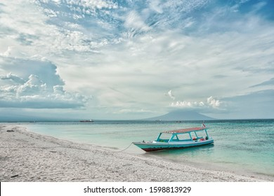 Seascape of tropical beach with turquoise water against dramatic sky and wooden boat moored at the shore