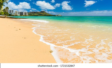 Seascape of a tropical pacific hawaiian beach with close-up of a calm turquoise ocean wave rolling in over the warm wet sand  - Diamond Head volcanic crater of world famous Waikiki beach in background