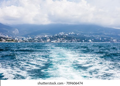 Seascape in the vicinity of the city of Yalta, Crimea. View from the sea to the shore and the mountains, to resort patios and boarding houses.