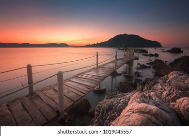 Seascape view of Jedi Ban Hua Leam wooden bridge in early morning with beautiful sunrise sky at Chanthaburi province Thailand