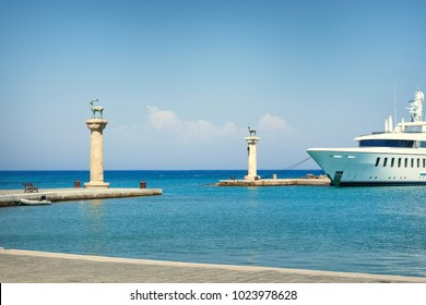Seascape view on deer statues and ship at the enrance to the Mandraki Harbour, where stood the Colossus of Rhodes, Greece