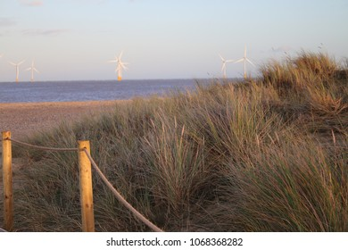 Seascape view over grassy sand dunes to beach and sea with ecologically friendly wind turbines in distance on north norfolk coast east anglia England in late afternoon with sunlight