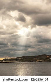 Seascape.  View of Syros coastline with a cloudy sky and sunbeam.