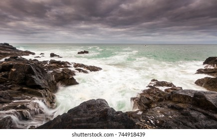 Seascape viewpoint from The Island, St ives, Cornwall with foreground rocks, breaking waves and small fishing boat on the horizon in stormy conditions