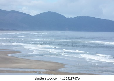 Seascape vista of the Oregon coast, with waves crashing on the sandy shore and mountains on the horizon