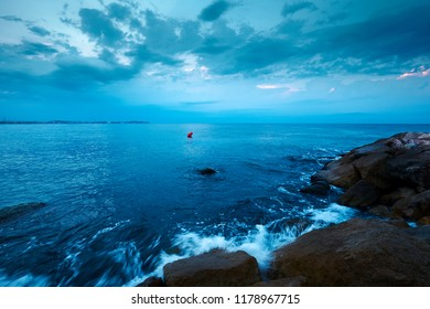 Seascape with waves crashing on the cliffs in the morning with cloudy sky and horizon line with red arrow shaped buoy in the center before sunrise