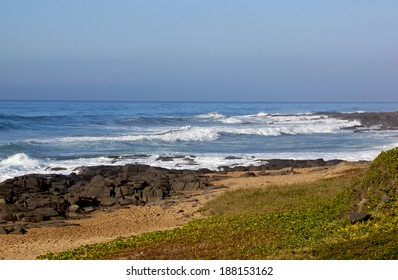 seascape of waves, rocks, sand and dunes on north coast of Durban South Africa