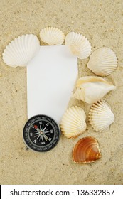 Seashell with compass and blank card on sand