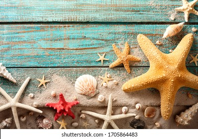 Seashell, starfish and beach sand on blue wooden background. Summer holiday concept. Top view.