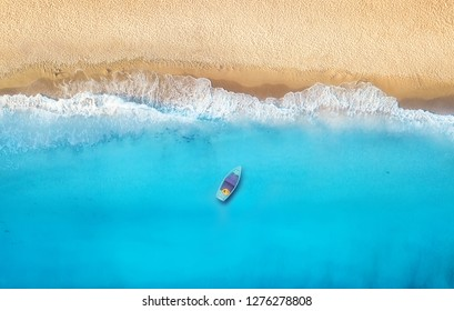 Seashore and boat from top view. Turquoise water background from top view. Summer seascape from air. Top view from drone. Travel concept and idea