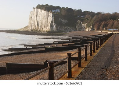 seashore landscape with breakwater constructions and houses on chalk cliffs in background