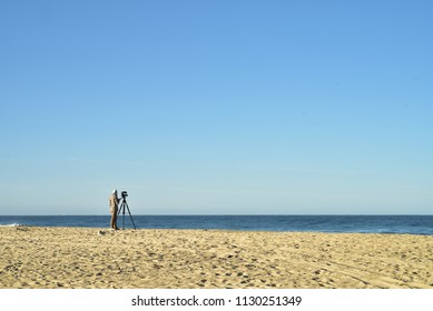seashore landscape with man standing next to video camera on tripod