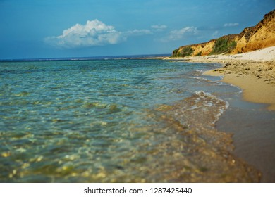 Seashore with transparent water and yellow rocks