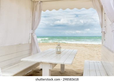 Seashore view through a white tent with table facing the sea