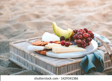 Seaside beach picnic on sand concept,  cheese platter with fruits - dark red grapes and melon and plums, crackers and nuts, copy space, relaxed resort eating, beautiful lifestyle concept