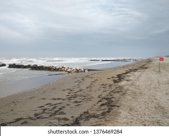 seaside beach with red flag - dangerous waves during strong wind