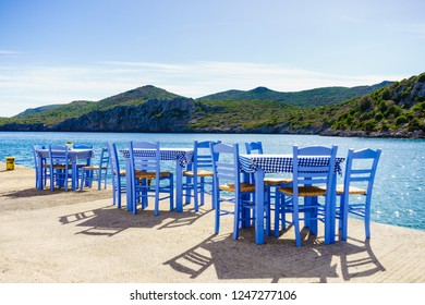 Seaside blue table and chairs open cafe outdoor restaurant in Greece on sea shore. Summer vacation on resort.