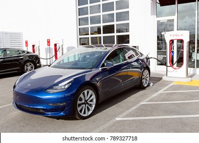 Seaside, CA - January 6, 2018: newest navy tesla model 3 charging at supercharger station