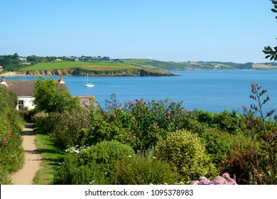 A seaside cottage and garden beside the coastal footpath with beautiful views at Portscatho, Cornwall, UK on a summer morning.